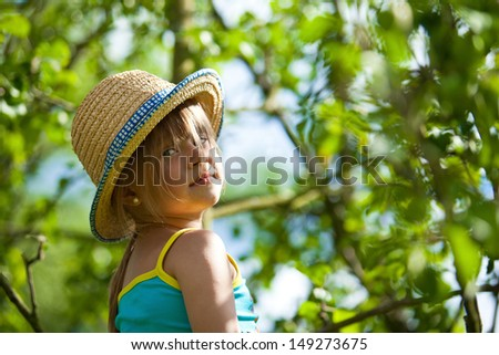 Little lovely girl posing in a straw hat in the park. - stock photo