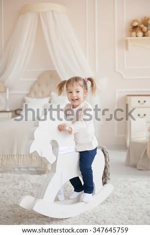 Little lovely smiling girl on the wooden toy horse in the interior of a child's room. - stock photo