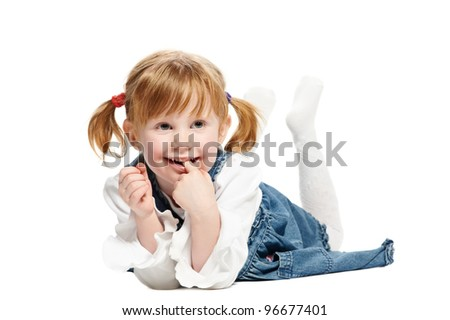 Little lying joyful girl with ponytails and risen foots on white background - stock photo