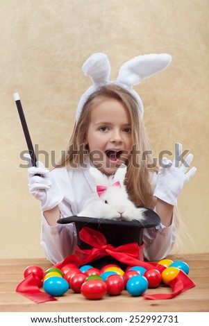 Little magician girl conjuring the easter bunny and colorful eggs- shallow depth of field - stock photo