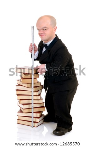Little man, dwarf teacher in a formal suit holding measure next stack of books, encyclopedia, studio shot, white background - stock photo