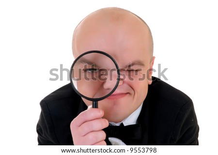 Little man, dwarf teacher in a formal suit looking trough magnifying glass, studio shot, white background
