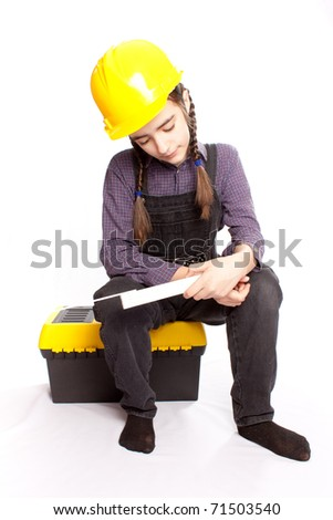 LIttle master girl sitting on tool box - stock photo