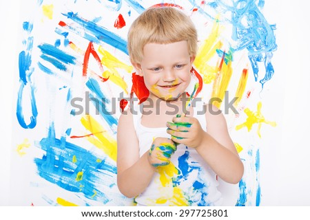 Little messy kid painting with paintbrush picture on easel. Education. Creativity. School. Preschool. Studio portrait over white background. - stock photo