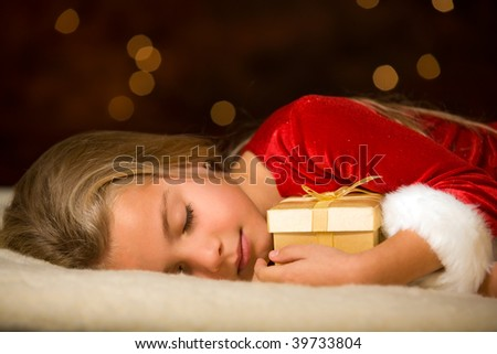 little miss santa asleep with a gift in her hand - stock photo