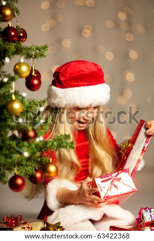 little miss santa sitting past the christmas tree and opening a gift - stock photo