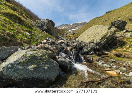 Little mountain streams from melting snow flowing in idyllic uncontaminated environment. Snowcapped mountain range in the background. Spring season in Piedmont, italian Alps. - stock photo