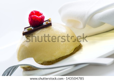 little mousse dessert with chocolate and raspberry as decoration on white background - stock photo