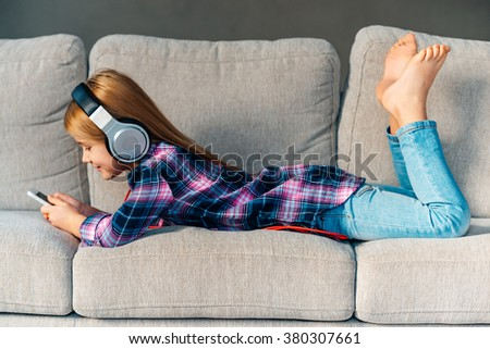 Little music lover. Beautiful little girl in headphones holding her smart phone with smile while lying on front on the couch at home - stock photo