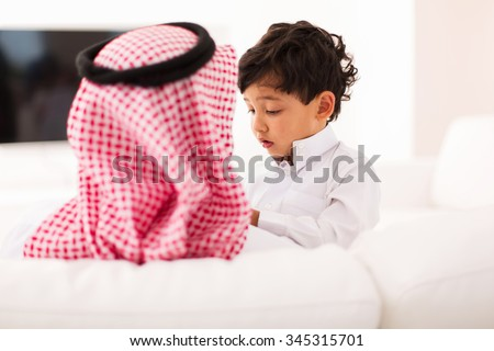 little muslim boy and his father spending time together at home - stock photo