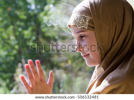 Little muslim girl looking through the window