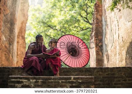Little Myanmar monk reading book, sitting outside monastery, Bagan, Myanmar - stock photo