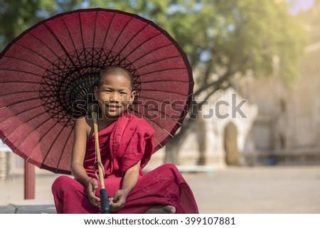 Little Myanmar monk sitting outside monastery, Bagan, Myanmar - stock photo