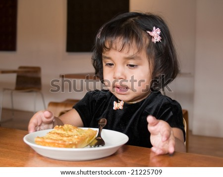 Little Native American girl getting ready to eat a slice of quiche in a coffee shop - stock photo