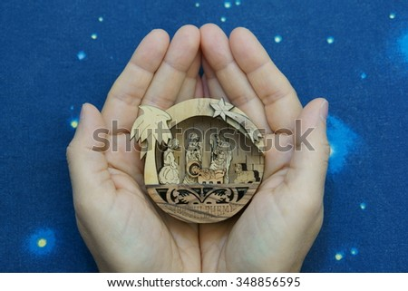 Little nativity scene (carved in wood) in the hands on blue sky background - stock photo