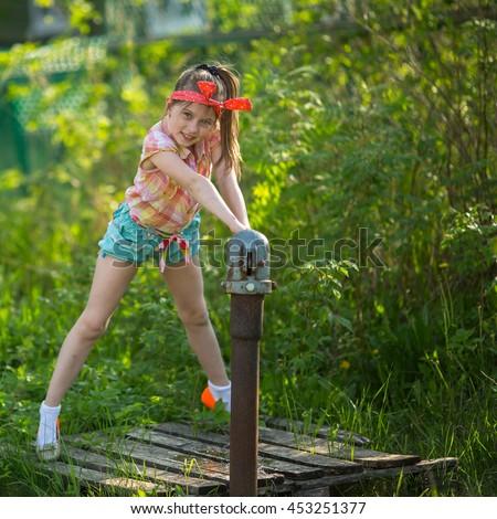 little naughty girl near water pump stock photo (royalty free