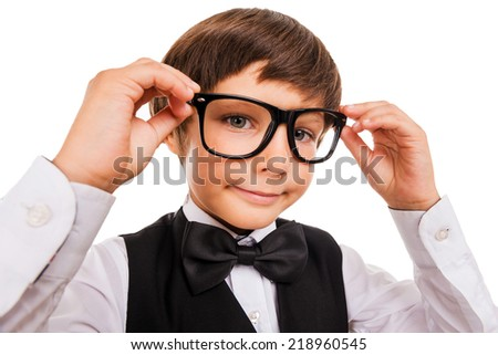Little Nerd. Wide angle image of cute little boy adjusting his glasses and looking at camera while isolated on white - stock photo