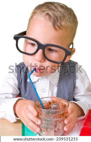 little nerd with glasses drinking chocolate milk - stock photo