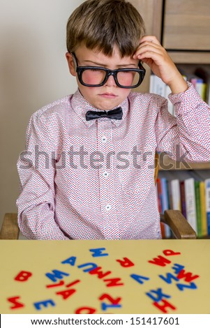little nerdy boy with geeky goggles thinking real hard. - stock photo
