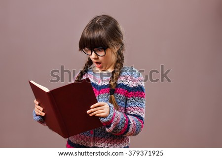 Little nerdy girl is surprised by something she has seen in her book. Surprised little nerdy girl - stock photo