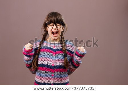 Little nerdy girl is very angry because of something.Angry little nerdy girl - stock photo