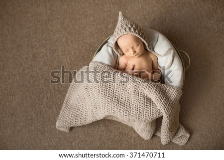 little newborn baby boy or girl in beige hat with close eyes sleeping sweetly under the blanket - stock photo