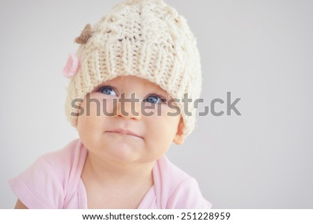 Little newborn baby girl in knitted hat. Parenting or love concept. Sad tired child. - stock photo