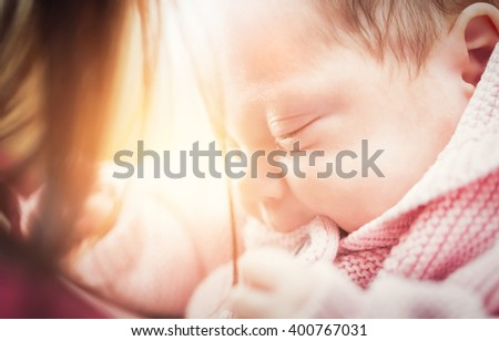 Little newborn baby in her mother arms. Close-up - stock photo