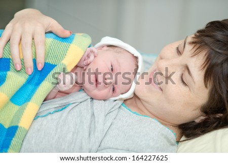 little newborn baby in the arms of mother. The baby after birth. birth in a hospital - stock photo