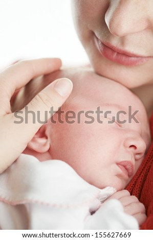 Little newborn baby lying on white blanket and under adult hand protection