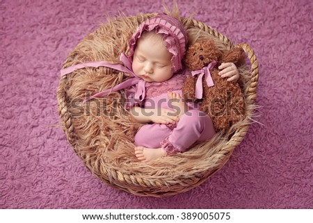 Little newborn girl 11 days, sleeps. Beautiful newborn girl wihh bear toy - stock photo