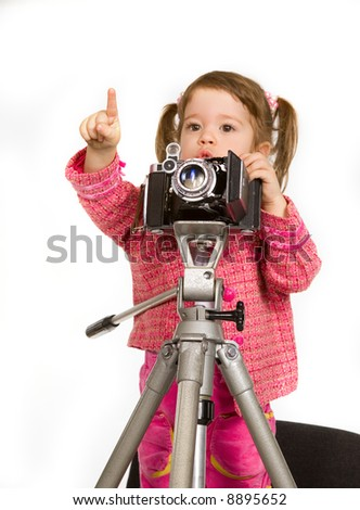Little nice caucasian model making a shot with camera on tripod - stock photo