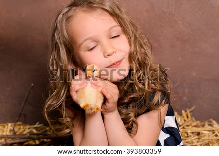 little nice smiling girl with wavy hair hugging alive chicken on brown wall background - stock photo