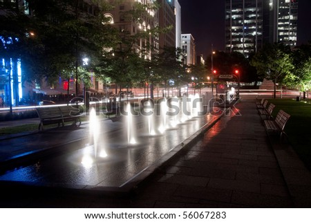 Little Night Fountain in the Middle of the Park in Old Montreal at Night and Office Building Background - stock photo