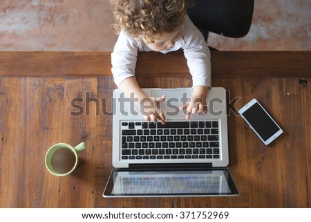 Little office worker. Toddler playing with laptop on wooden table - stock photo