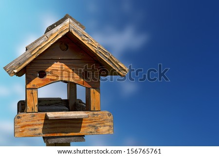 Little Old Birdhouse on Blue Sky / Old wooden birdhouse on a blue and blurred sky with free space for text - stock photo