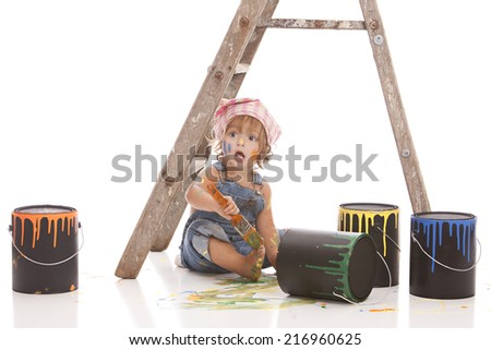 Little painter.  Adorable little girl sitting on the floor next to paint can and a ladder and holding a paintbrush.  Isolated on white with room for your text. - stock photo