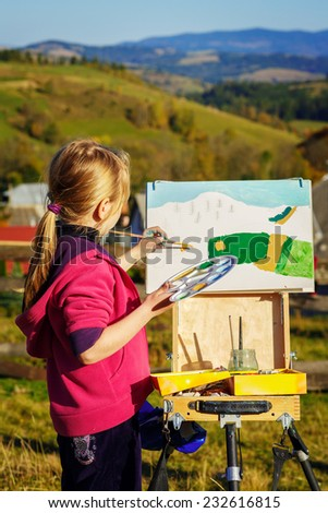 little painter at work in the mountains with palette - stock photo