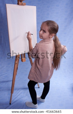 Little painter stay near easel - stock photo