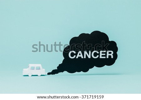 Little paper car creating toxic and unhealthy smoke while running. - stock photo