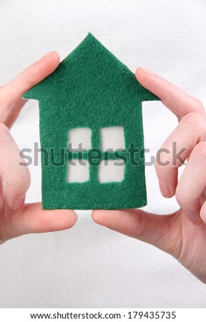 Little paper house in hand close-up