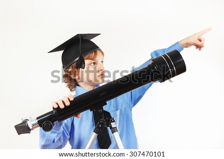 Little pensive boy in academic hat with telescope on a white background - stock photo