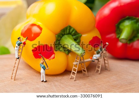 Little people paint pepper to another color. The concept of teamwork and cooking. - stock photo