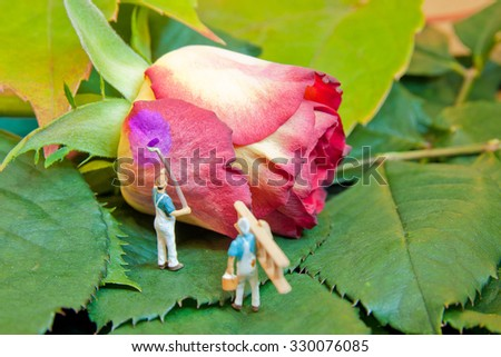 Little people paint rose to another color. The concept of teamwork. - stock photo