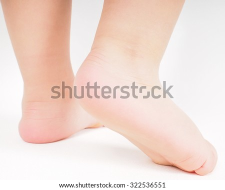 Little person walking away barefoot towards bright background - stock photo