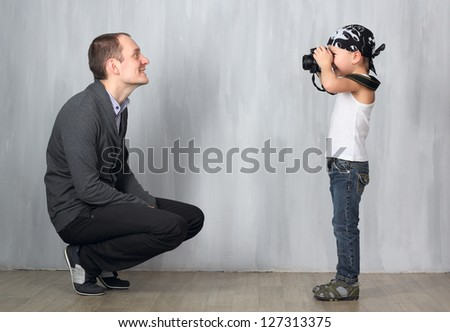 Little photographer takes a photo of a man