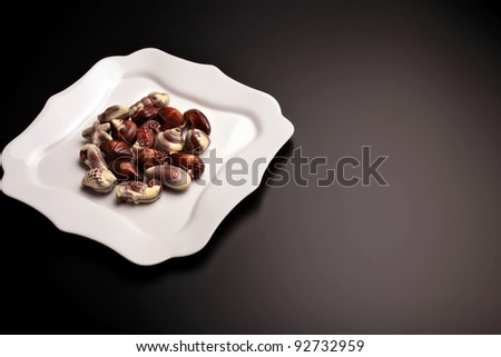 Little pieces of chocolate seashells on white fancy plate, isolated on black background - stock photo