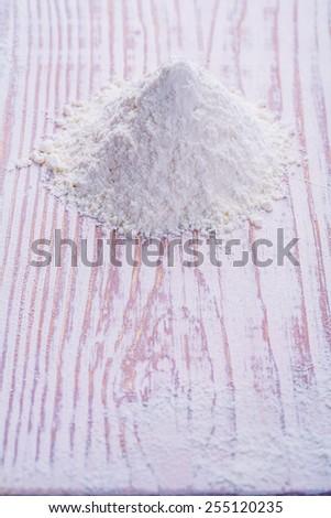 little pile of flour on old white desk - stock photo