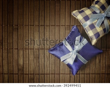 Little pillow with ribbon bow on Japanese style bamboo pad - stock photo
