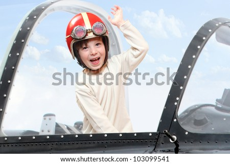 Little pilot in cockpit of a vintage plane. Close up with shallow DOF. - stock photo